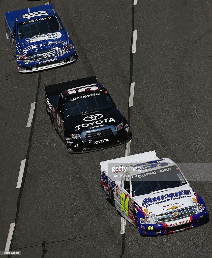 Chase Elliott, driver of the #94 Aaron's Dream Machine/Hendrickcars.com Chevrolet, leads Erik Jones, driver of the #51 Toyota Care Toyota, and Ross Chastain, driver of the #19 Brad Keselowski's Checkered Flag Foundation, into turn one during the NASCAR Camping World Truck Series Kroger 250 on April 6, 2013 at Martinsville Speedway in Ridgeway, Virginia.