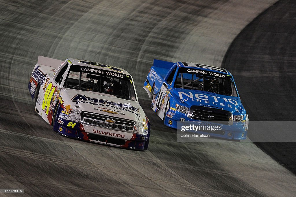 Chase Elliott, driver of the #94 Aaron's Dream Machine/Hendrickcars.com Chevrolet, races with German Quiroga, driver of the #77 NET 10 Wireless Toyota during the Camping World Truck Series UNOH 200 at Bristol Motor Speedway on August 21, 2013 in Bristol, Tennessee.