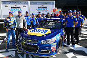 Chase Elliott driver of the NAPA Auto Parts Chevrolet and his crew members pose in Victory Lane after winning the pole award during qualifying for...