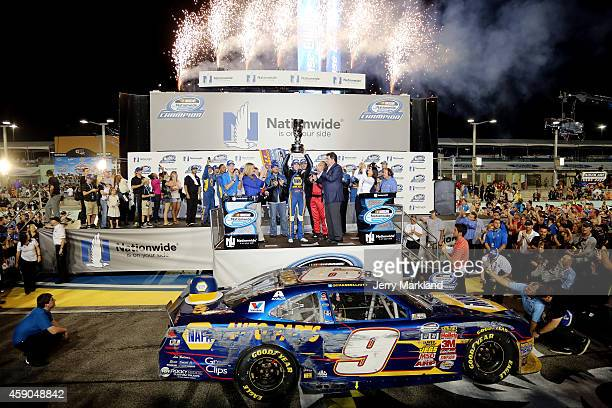 Chase Elliott driver of the NAPA Auto Parts Chevrolet celebrates with the trophy in Victory Lane after winning the series championship during the...