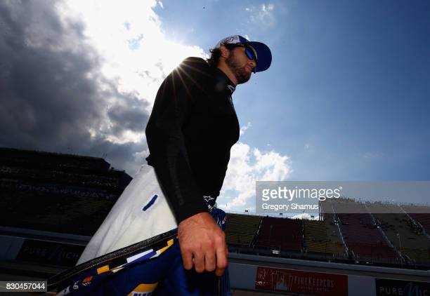 Chase Elliott driver of the NAPA Chevrolet walks on the grid during qualifying for the Monster Energy NASCAR Cup Series Pure Michigan 400 at Michigan...