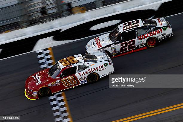 Chase Elliott driver of the TaxSlayercom Chevrolet takes the checkered flag ahead of Joey Logano driver of the Discount Tire Ford to win the NASCAR...