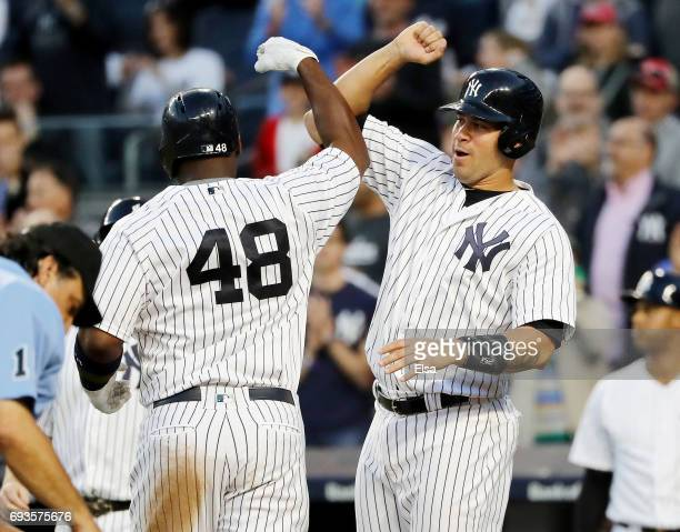 Chase Headley congratulates teammate Chris Carter of the New York Yankees after Carter drove them all home with a three run home run in the fourth...