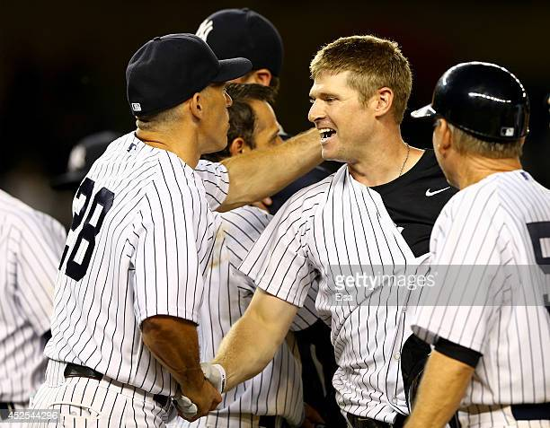 Chase Headley of the New York Yankees is congratulated by manager Joe Girardi after Headley drove in the game winning run against the Texas Rangers...