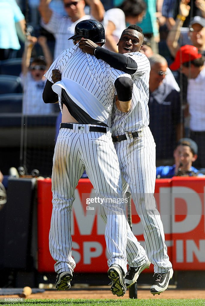 Chase Headley #12 of the New York Yankees is congratulated by teammate Didi Gregorius #18 after Headley scores on a passed ball in the ninth inning against the Texas Rangers at Yankee Stadium on June 30, 2016 in the Bronx borough of New York City. The New York Yankees defeated the Texas Rangers 2-1.