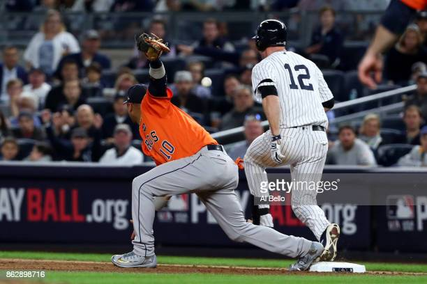 Chase Headley of the New York Yankees reaches first as Yuli Gurriel of the Houston Astros fails to field the throw during the fifth inning in Game...