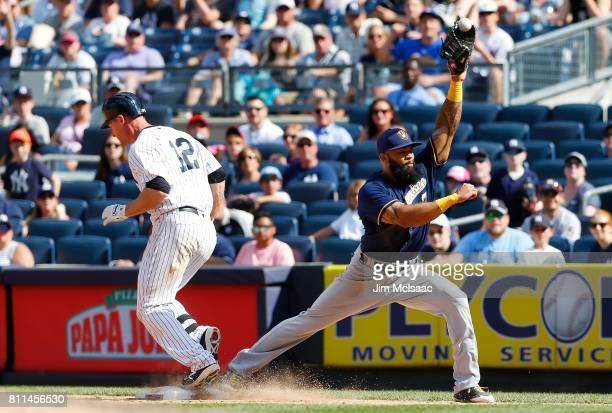 Chase Headley of the New York Yankees reaches first base as Eric Thames of the Milwaukee Brewers can't come up with the throw during the eighth...