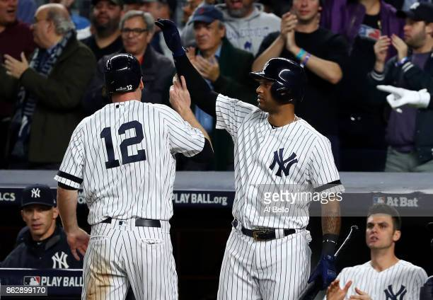 Chase Headley of the New York Yankees reacts with Aaron Hicks after scoring on a single by Gary Sanchez during the fifth inning against the Houston...