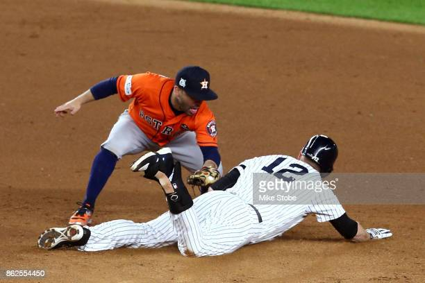 Chase Headley of the New York Yankees slides in to second after hitting a single during the eighth inning as Jose Altuve of the Houston Astros...