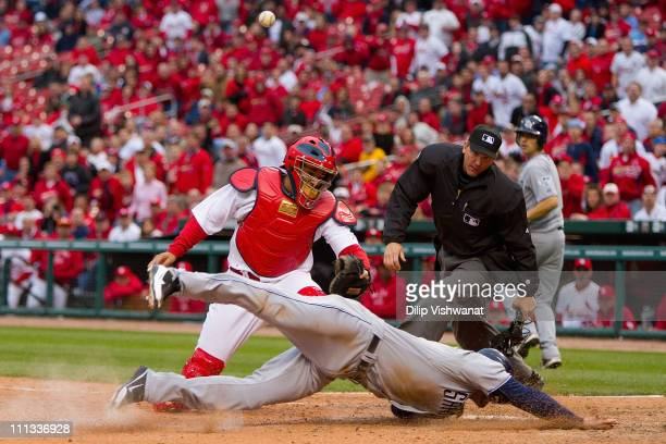 Chase Headley of the San Diego Padres scores the gamewinning run against Yadier Molina of the St Louis Cardinals as umpire Jeff Kellogg on opening...