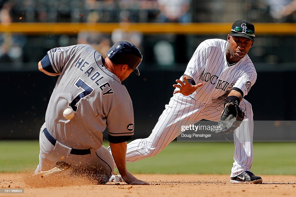 Chase Headley of the San Diego Padres slides safely into second base with a stolen base as the pick off throw hits him in the back as second baseaman...