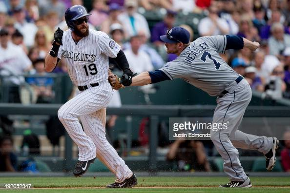 Chase Headley of the San Diego Padres tags out Charlie Blackmon of the Colorado Rockies during a run down for the second out of the seventh inning at...