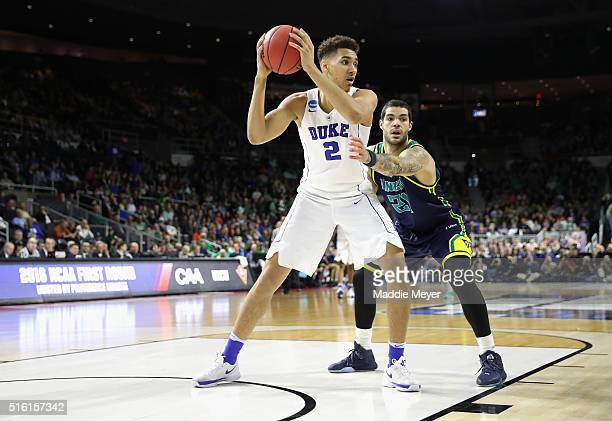 Chase Jeter of the Duke Blue Devils handles the ball as he is defended by Marcus Bryan of the North CarolinaWilmington Seahawks in the first half of...