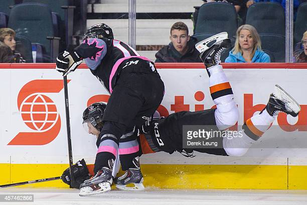 Chase Lang of the Calgary Hitmen checks Cale Fleury of the Medicine Hat Tigers during a WHL game at Scotiabank Saddledome on October 18 2014 in...