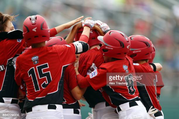 Chase Marshall of the Canada team from British Columbia is surrounded by his teammates after hitting a home run during Game 3 of the 2017 Little...