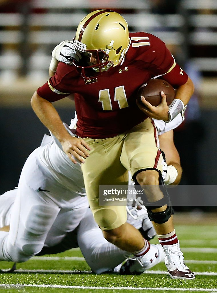 Chase Rettig #11 of the Boston College Eagles has his face mask grabbed by a Wake Forest Demon Deacons defender in the third quarter during the game on September 6, 2013 at Alumni Stadium in Chestnut Hill, Massachusetts.