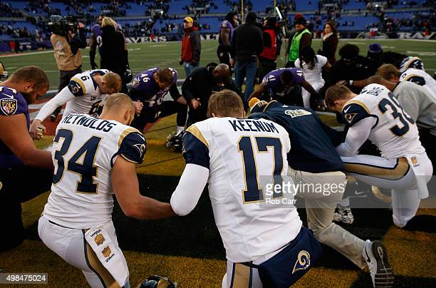 Chase Reynolds and Case Keenum of the St Louis Rams pray with members of the Baltimore Ravens following the Rams 1613 loss at MT Bank Stadium on...