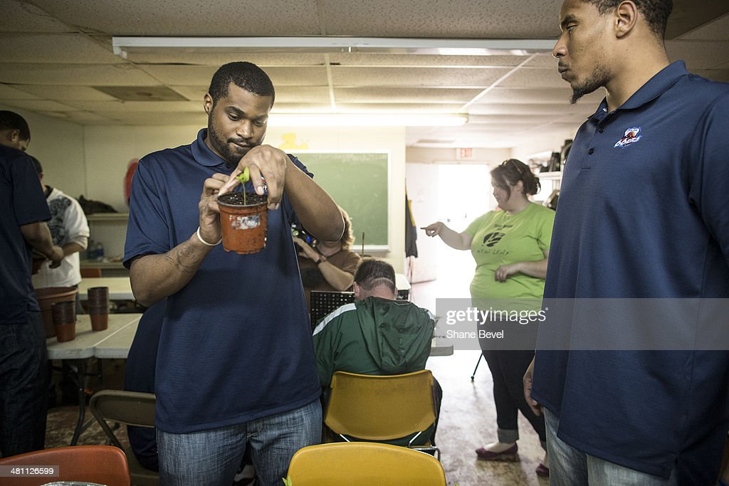 Chase Tarpley and Ron Anderson of the Tulsa 66ers repot plants while volunteering during the NBA D-League community relations event at A New Leaf, a non-profit that employs adults with developmental disabilities, on March 27, 2014 in Broken Arrow, Oklahoma.