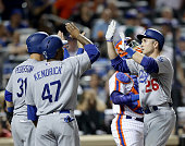 Chase Utley of the Los Angeles Dodgers celebrates his grand slam with teammates waiting at home plate in the seventh inning against the New York Mets...