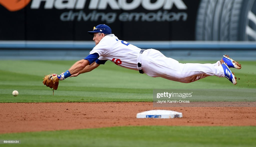 Chase Utley #26 of the Los Angeles Dodgers dives for a single by Jose Peraza #9 of the Cincinnati Reds in the second inning of the game at Dodger Stadium on June 11, 2017 in Los Angeles, California.