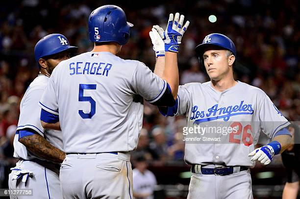Chase Utley of the Los Angeles Dodgers is greeted at home by Howie Kendrick and Corey Seager after hitting two run home run in the seventh inning...