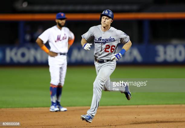 Chase Utley of the Los Angeles Dodgers rounds the bases as Amed Rosario of the New York Mets looks on after Utley hit a two run home run in the sixth...