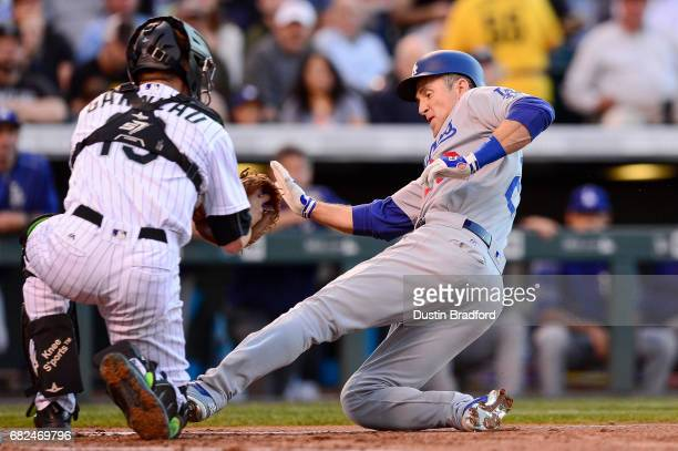 Chase Utley of the Los Angeles Dodgers slides into a tag by Dustin Garneau of the Colorado Rockies attempting to score on a sacrifice bunt in the...