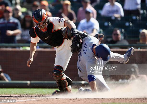 Chase Utley of the Los Angeles Dodgers slides under the tag of Nick Hundley of the San Francisco Giants to score on a sacrifice fly hit by Enrique...