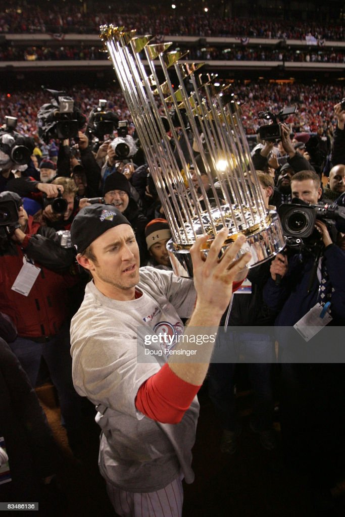 Chase Utley of the Philadelphia Phillies celebrates with the World Series trophy after their 43 win against the Tampa Bay Rays during the...