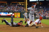 Chase Utley of the Philadelphia Phillies gets tagged out at home plate in the eighth by Jhonatan Solano of the Washington Nationals as pitcher Craig...