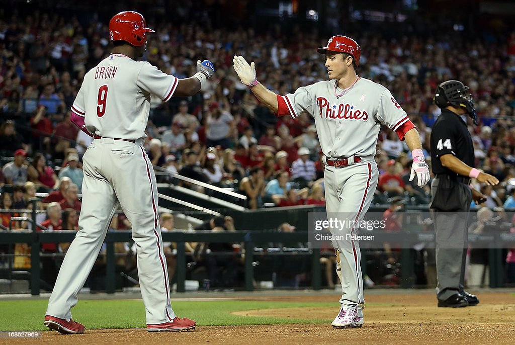 <a gi-track='captionPersonalityLinkClicked' href=/galleries/search?phrase=Chase+Utley&family=editorial&specificpeople=161391 ng-click='$event.stopPropagation()'>Chase Utley</a> #26 of the Philadelphia Phillies high fives <a gi-track='captionPersonalityLinkClicked' href=/galleries/search?phrase=Domonic+Brown&family=editorial&specificpeople=6900643 ng-click='$event.stopPropagation()'>Domonic Brown</a> #9 after scoring a ninth inning run against the Arizona Diamondbacks during the MLB game at Chase Field on May 12, 2013 in Phoenix, Arizona.