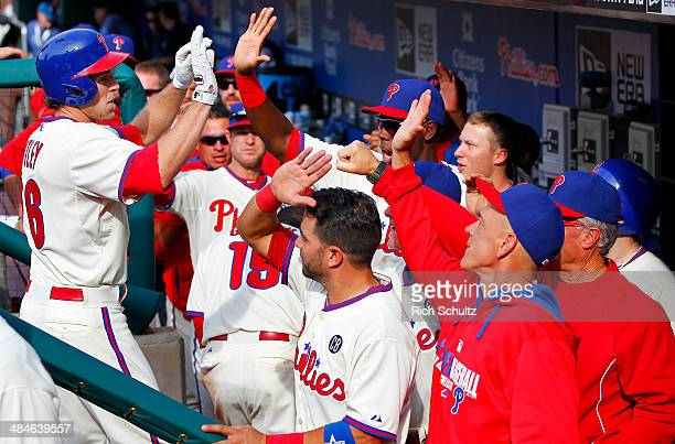 Chase Utley of the Philadelphia Phillies is congratulated by teammates after hitting the go ahead home run in the eighth inning against the Miami...
