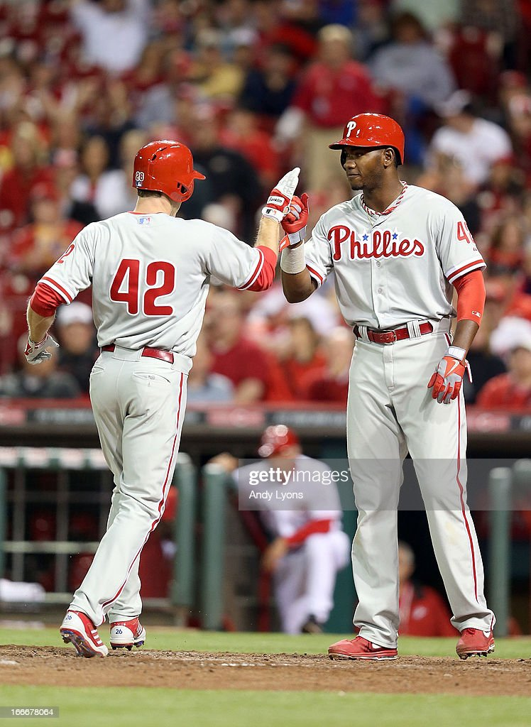 <a gi-track='captionPersonalityLinkClicked' href=/galleries/search?phrase=Chase+Utley&family=editorial&specificpeople=161391 ng-click='$event.stopPropagation()'>Chase Utley</a> of the Philadelphia Phillies is congratulated by <a gi-track='captionPersonalityLinkClicked' href=/galleries/search?phrase=Domonic+Brown&family=editorial&specificpeople=6900643 ng-click='$event.stopPropagation()'>Domonic Brown</a> after Utley hit a home run in the 8th inning during the game against the Cincinnati Reds at Great American Ball Park on April 15, 2013 in Cincinnati, Ohio. All uniformed team members are wearing jersey number 42 in honor of Jackie Robinson Day.