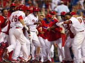 Chase Utley of the Philadelphia Phillies is mobbed by teammates after hitting a tworun walkoff home run in the 14th inning to defeat the Miami...