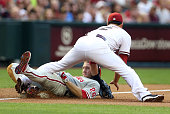 Chase Utley of the Philadelphia Phillies is tagged out by infielder Eric Chavez of the Arizona Diamondbacks as he attempts to stretch a double into a...