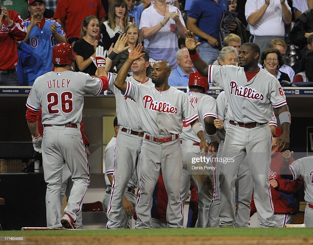 Chase Utley #26 of the Philadelphia Phillies, left, is congratulated by teammates after scoring during the 13th inning of a baseball game against the San Diego Padres at Petco Park on June 26, 2013 in San Diego, California. The Phillies won 7-5.