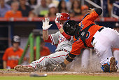 Chase Utley of the Philadelphia Phillies slides into home plate ahead of the tag from Jhonatan Solano of the Miami Marlins during the sixth inning of...