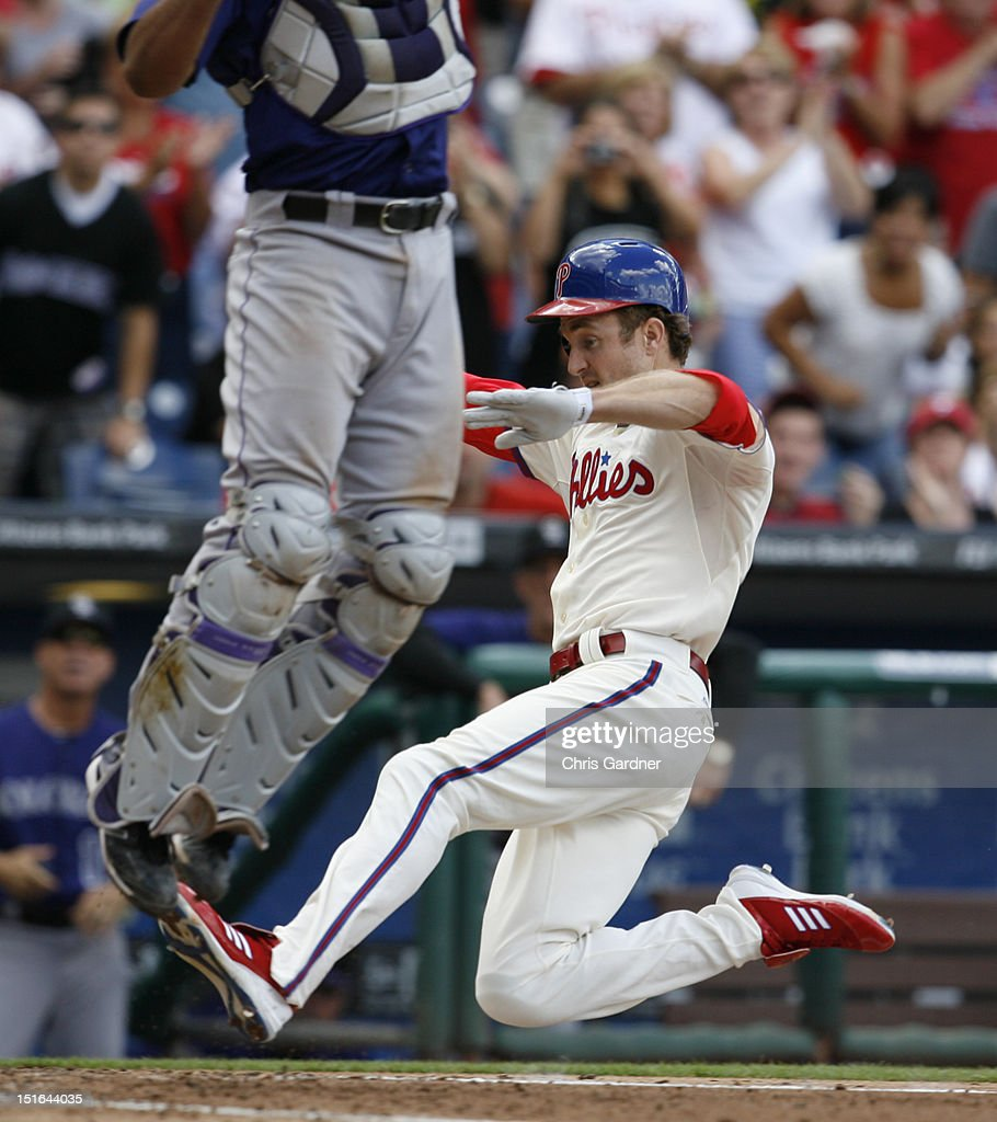 <a gi-track='captionPersonalityLinkClicked' href=/galleries/search?phrase=Chase+Utley&family=editorial&specificpeople=161391 ng-click='$event.stopPropagation()'>Chase Utley</a> #26 of the Philadelphia Phillies slides into home plate as catcher <a gi-track='captionPersonalityLinkClicked' href=/galleries/search?phrase=Wilin+Rosario&family=editorial&specificpeople=5734314 ng-click='$event.stopPropagation()'>Wilin Rosario</a> #20 of the Colorado Rockies leaps for the throw at Citizens Bank Park on September 9, 2012 in Philadelphia, Pennsylvania.