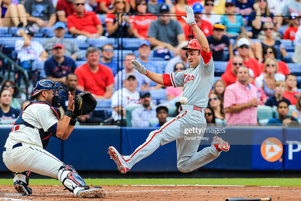 <a gi-track='captionPersonalityLinkClicked' href=/galleries/search?phrase=Chase+Utley&family=editorial&specificpeople=161391 ng-click='$event.stopPropagation()'>Chase Utley</a> #26 of the Philadelphia Phillies slides into home to score before <a gi-track='captionPersonalityLinkClicked' href=/galleries/search?phrase=Gerald+Laird&family=editorial&specificpeople=228949 ng-click='$event.stopPropagation()'>Gerald Laird</a> #11 of the Atlanta Braves can make the tag in the fourth inning at Turner Field on September 29, 2013 in Atlanta, Georgia.