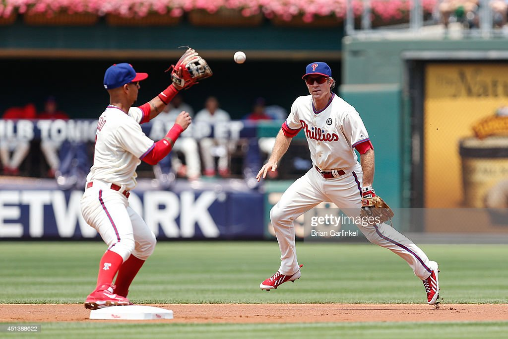 <a gi-track='captionPersonalityLinkClicked' href=/galleries/search?phrase=Chase+Utley&family=editorial&specificpeople=161391 ng-click='$event.stopPropagation()'>Chase Utley</a> #26 of the Philadelphia Phillies tosses the ball to <a gi-track='captionPersonalityLinkClicked' href=/galleries/search?phrase=Ronny+Cedeno&family=editorial&specificpeople=546778 ng-click='$event.stopPropagation()'>Ronny Cedeno</a> #7 to turn a double play in the first inning of the first game of a doubleheader against the Atlanta Braves at Citizens Bank Park on June 28, 2014 in Philadelphia, Pennsylvania.