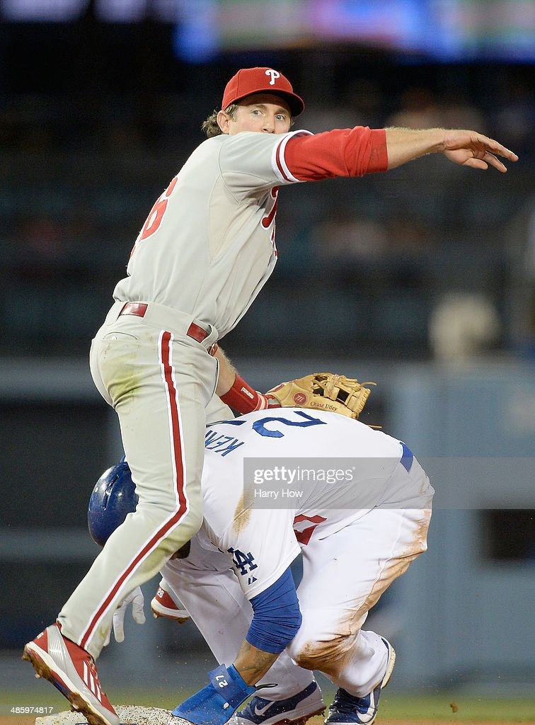 <a gi-track='captionPersonalityLinkClicked' href=/galleries/search?phrase=Chase+Utley&family=editorial&specificpeople=161391 ng-click='$event.stopPropagation()'>Chase Utley</a> #26 of the Philadelphia Phillies watches his throw to first as he lands on <a gi-track='captionPersonalityLinkClicked' href=/galleries/search?phrase=Matt+Kemp&family=editorial&specificpeople=567161 ng-click='$event.stopPropagation()'>Matt Kemp</a> #27 of the Los Angeles Dodgers after his throw during the second inning at Dodger Stadium on April 21, 2014 in Los Angeles, California.