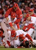 Chase Utley Ryan Howard and Geoff Jenkins of the Philadelphia Phillies pile on top of closing pitcher Brad Lidge and catcher Carlos Ruiz after they...
