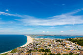 Aerial view on Chesil Beach, marina and Fortuneswell town on Isle of Portland, UK. Horizontal crop, low horizon. Sunny day, blue sky and azure water