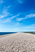 Low wide angle view on Chesil Beach on Isle of Portland, UK. Blue clear sky and azure water. Vertical crop