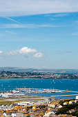 Aeial view on marina ad Fortuneswell on Isle of Portland. Bue clear sky, azure water, low horizon. Vertical crop