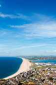 Aerial view on Chesil Beach, marina and Fortuneswell town on Isle of Portland, UK. Vertical crop, low horizon. Sunny day, blue sky and azure water