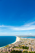 Aerial view on Chesil Beach, Fortuneswell and marina on Isle of Portland, UK. Vertical crop, low horizon in sunny summer day, blue sky and azure sea.