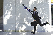 Businessman with umbrella running to catch taxi or bus