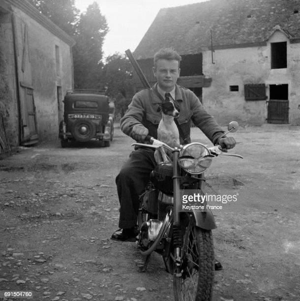 Chasseur partant à la chasse sur sa moto son chien avec lui en Normandie France en 1954