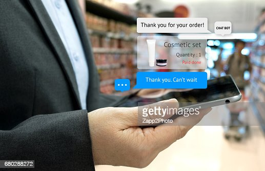 Chat bot and future marketing concept . Customer hand holding tablet for order cosmetic set and popup out tablet screen with automatic chatbot message screen , supermarket retail background : Stock Photo